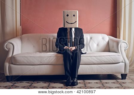 Businessman sitting on Sofa mit Kopf im Feld