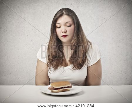 sad young woman looking hot dog
