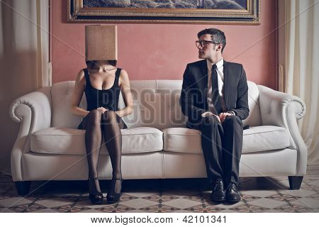 man looks at beautiful woman with box on his head sitting on the couch