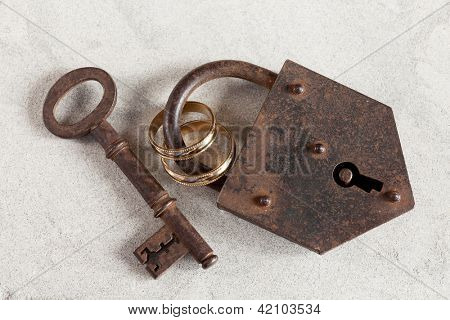 Wedding rings boud by a rusty old padlock