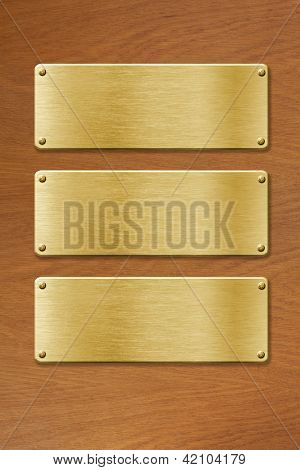 three golden metal plates over wood texture
