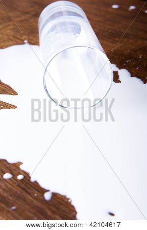 Milk spilled from glass on wooden surface