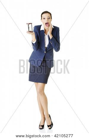 Young shocked business woman with hourglass - time concept