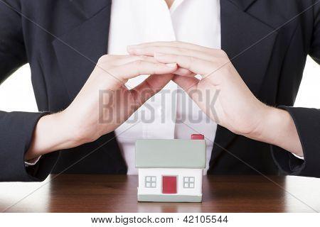 Empresária com modelo de casa sobre branco - conceito de empréstimo imobiliário