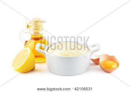 Bowl of mayonnaise with the main ingredients, oil, eggs and lemons