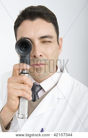 Portrait of male doctor looking through an ophthalmoscope