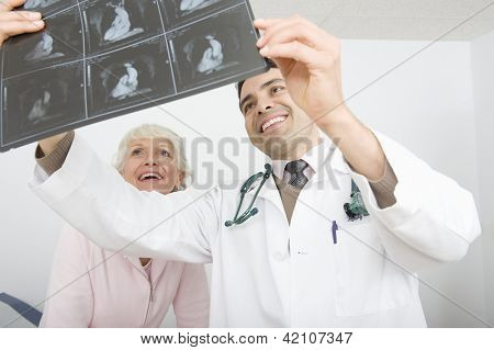 Happy male doctor explaining x-ray to patient