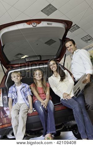 Family sitting at back of car is showroom