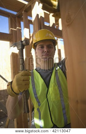 Confident young worker hammering at construction site