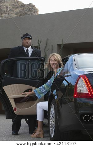 Happy woman sitting in luxury car while chauffeur standing nearby