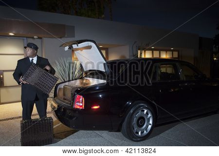 Chauffeur loading luggage in car at night