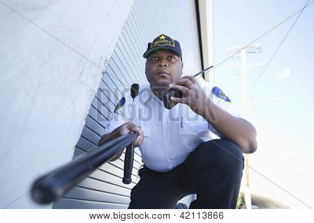Low angle view of security guard holding a baton