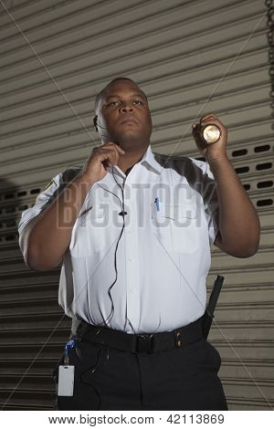 Security guard with torch patrols on duty