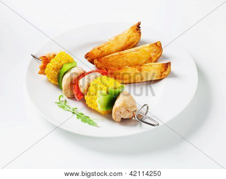 meat and vegetable skewer with potatoes as a side dish