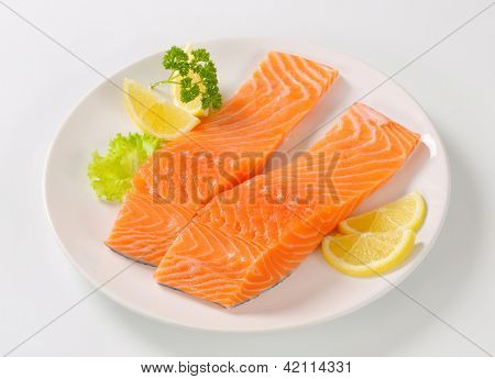 two salmon steaks with sliced lemon and parsley, on the round plate