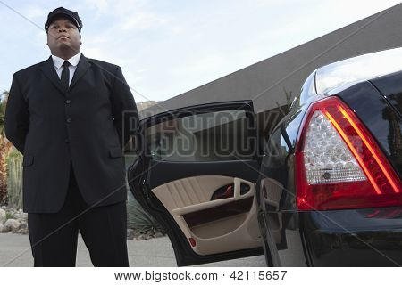 Mixed race chauffeur standing by luxury car