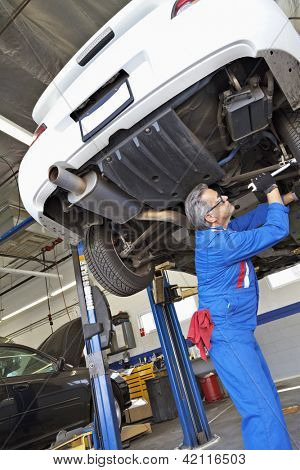 Low angle view of middle-aged mechanic working under car