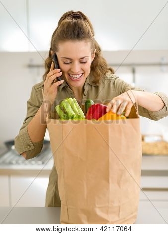 Young Housewife Sort Purchases After Shopping And Talking Cell P