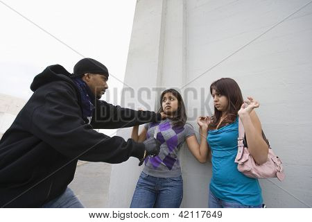 An aggressive male robber scaring two young girls with a knife