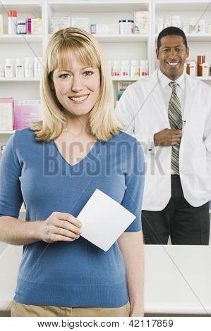 Retrato de un cliente mujer feliz celebración de prescripción con el farmacéutico en el fondo