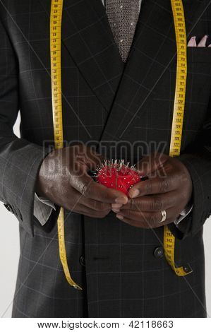 Mid section of man wearing suit holding pincushion