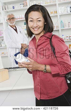 Retrato de un cliente mujer feliz celebración de medicina y prescripción con el farmacéutico en el centrico