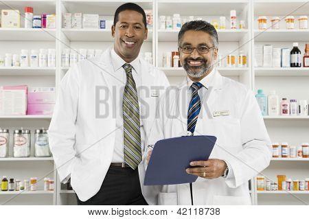 Retrato de una media de edad farmacéutico hombre sosteniendo el pie del portapapeles con el compañero de trabajo en el lugar de trabajo