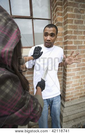 A young female criminal scaring young man with a knife