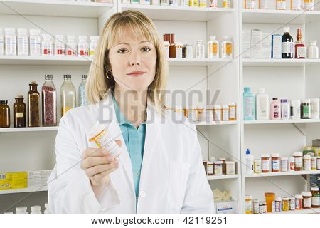 Portrait of a confident female pharmacist prescribing medicine at workplace with medicines in the background