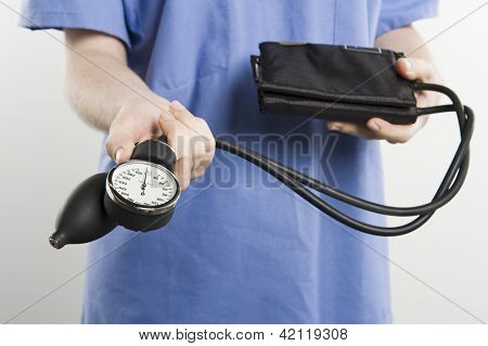 Midsection of a female nurse holding blood pressure equipment isolated over white background