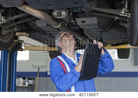 Mechanic scrutinizing the car and writing down something on clipboard