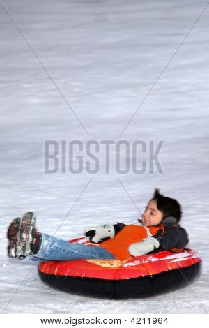 Boy Tubing Down Snowy Hill