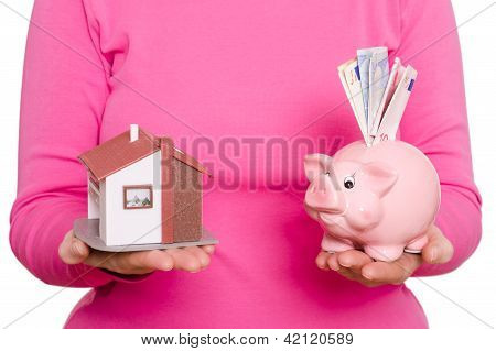 House And Piggy Bank In A Hand