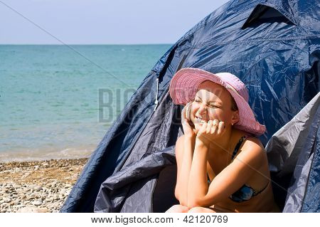 Girl calls by phone, sitting in tent