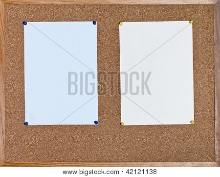 Two Sheets Of Paper On Cork Board