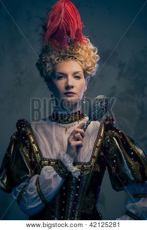 Haughty queen in royal dress with mirror