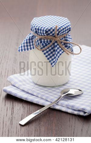 Homemade Milk Yogurt In Glass Pot And Spoon On Table