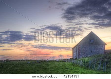 Velho celeiro na paisagem ao pôr do sol