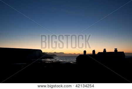 Silhouette Of Coastguard Cottages At Seaford Head At Sunrise