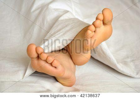 sleeping teen girl feet under the blanket