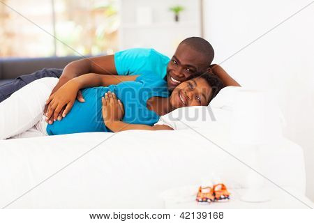 expecting african american couple lying on bed