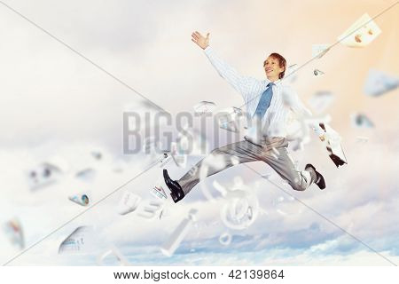 Image of a businessman jumping high against blue sky background