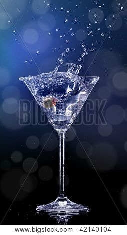 Martini drink splashing out of glass