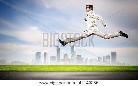 Jovem empresário de terno correndo na estrada
