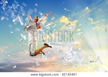 Image of a businesswoman jumping high against blue sky background