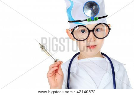 Portrait of a cute boy in big spectacles playing doctor with syringe and a stethoscope. Isolated over white.