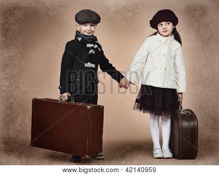 Bonito menino e uma menina de pé com suas malas de viagem antigas. Estilo retrô.