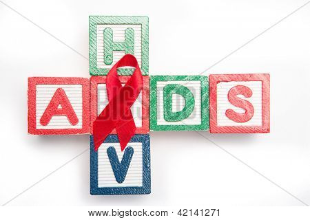 Wood blocks spelling aids and hiv in a cross shape with red awareness ribbon on white background