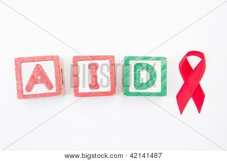 Wood blocks spelling out aids in green and red with awareness ribbon on white background