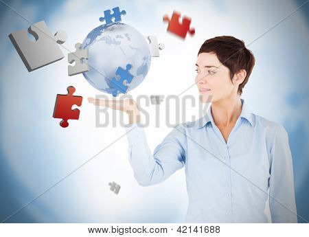 Cheerful woman with puzzles and a globe levitating